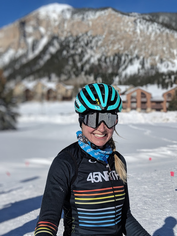 Fat bike rider smiling in front of a snowy mountainous backdrop