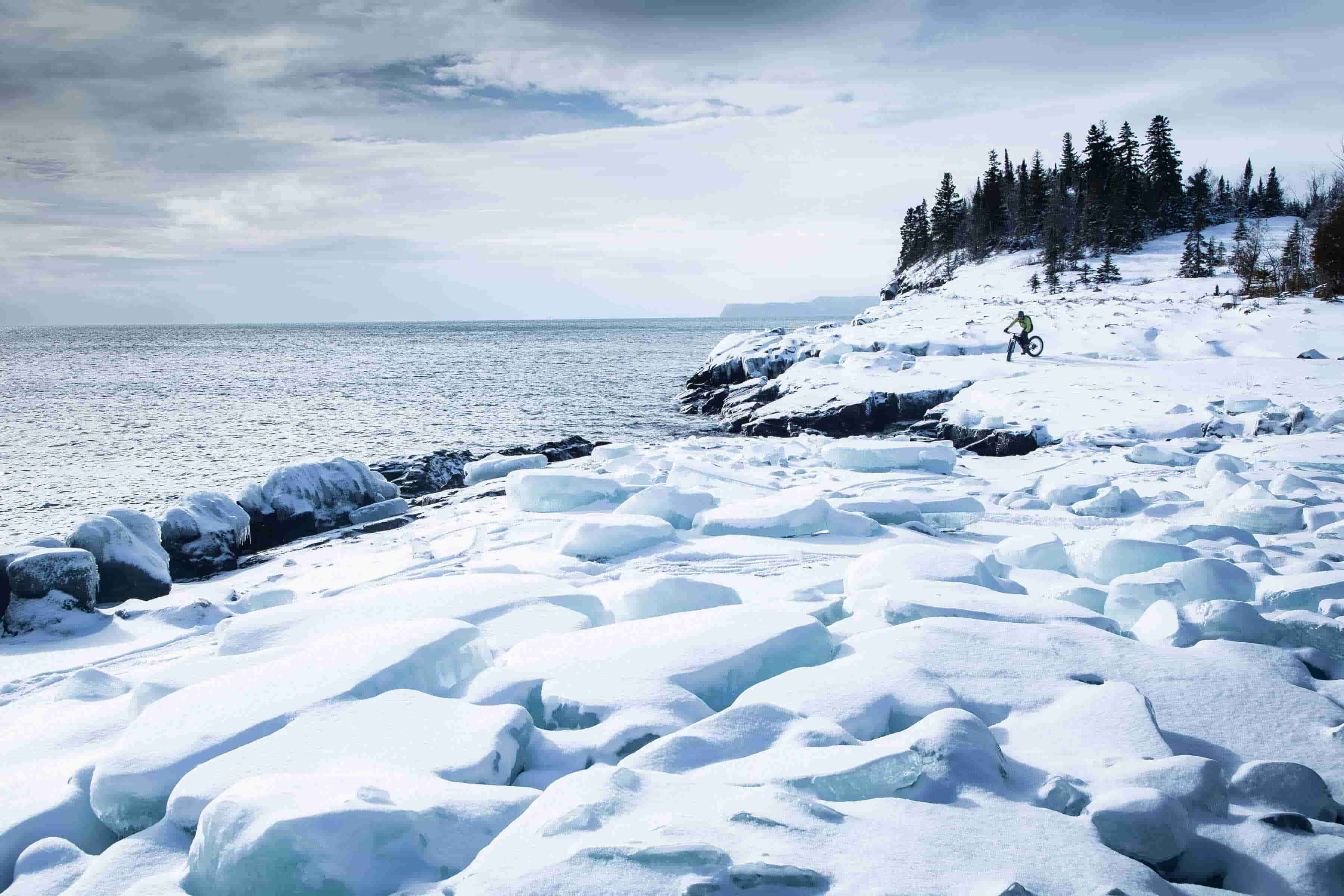 Icy shoreline covered in snow with fat bike rider in the distance