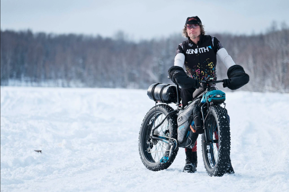 Person in a black 45NRTH jacket stands next to their fat bike surrounded by snow