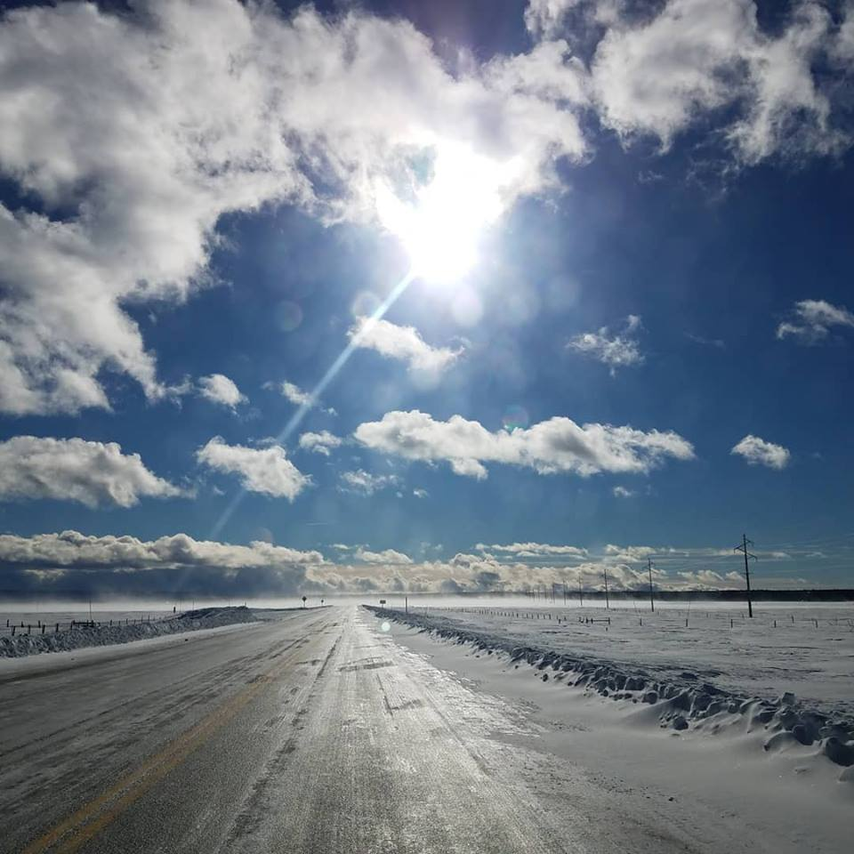 Empty two-lane road with sunny blue skies and puffy clouds above