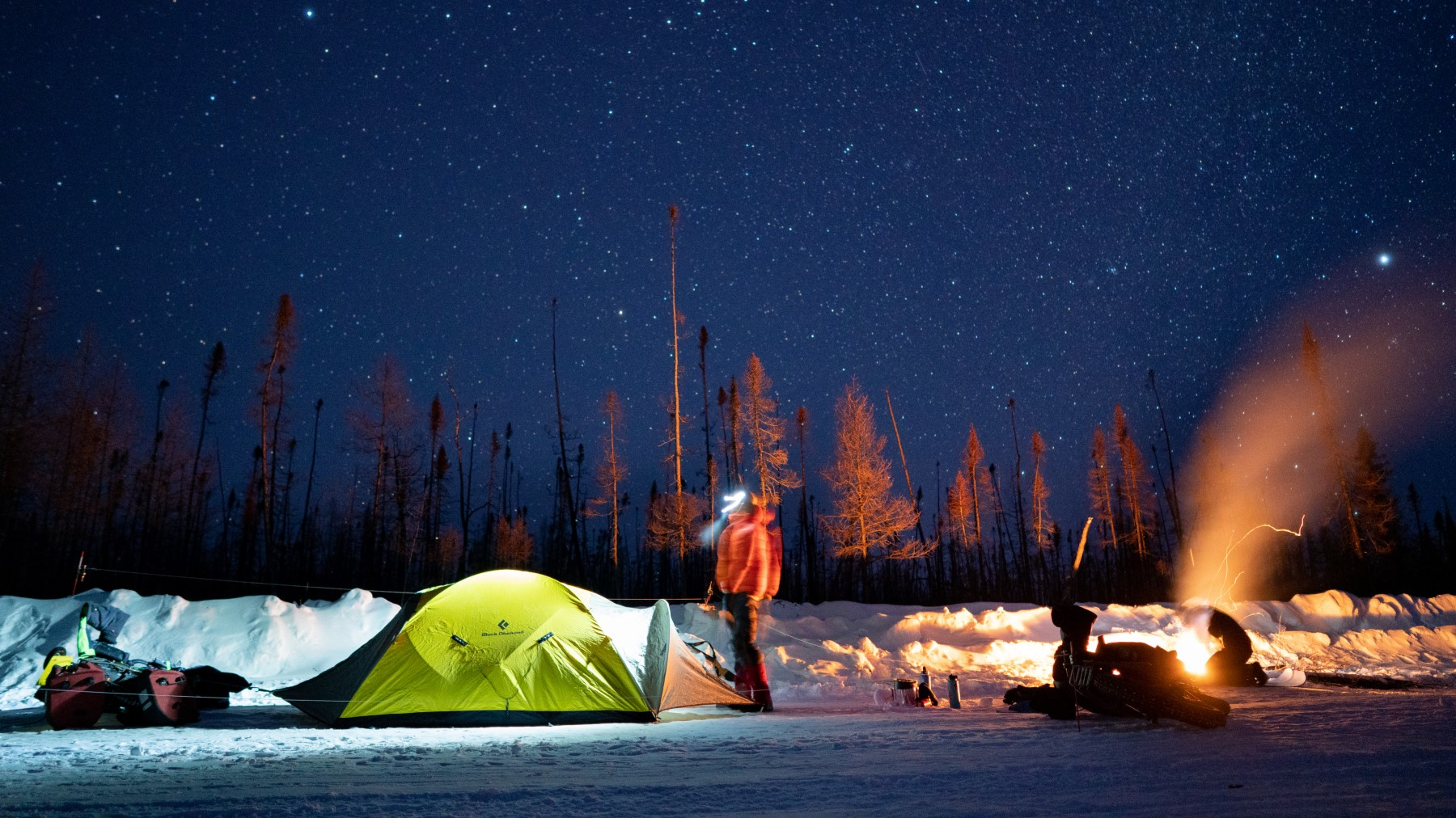 Riders setting up tents and fire at campsite in the snow at night