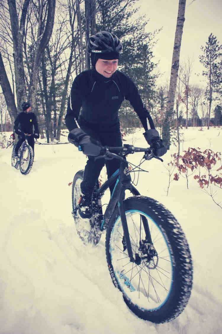 A woman riding a fat bike over a snow-covered trail