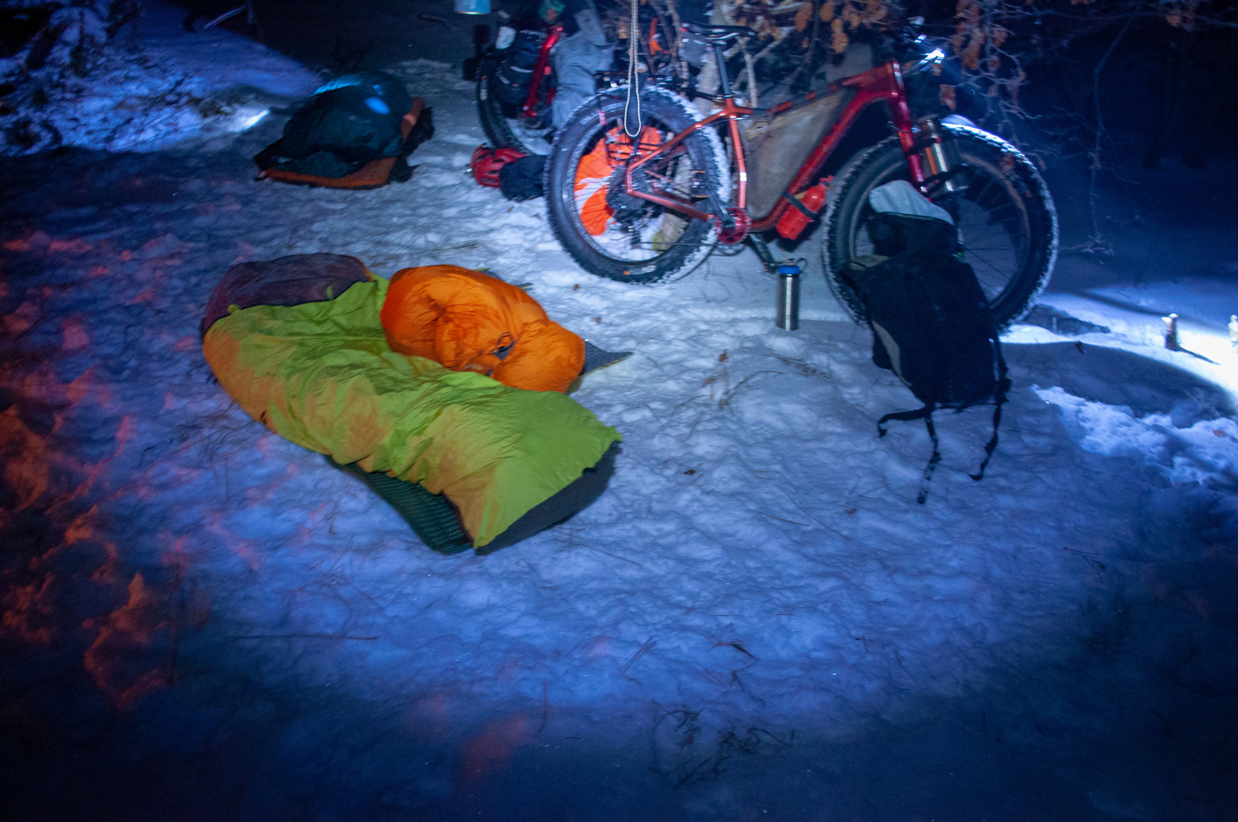 Sleeping bags set up in the snow in front of fat bikes at night