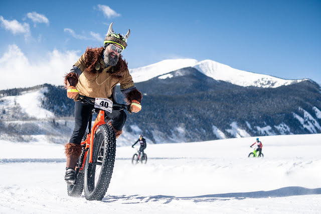 Fat bike cyclist in Viking-style costume on the race course