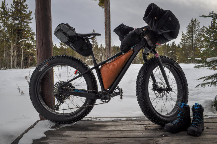 Fat bike loaded with pogies, frame pack, and seat pack in front of snow and trees