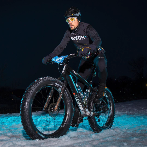 Man in a black 45NRTH jacket riding his fat bike on snow in a blue lights