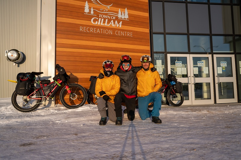 Three riders in winter cycling gear kneeling in front of entrance to Gillam Recreation Centre