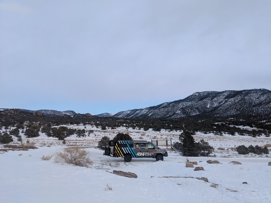 The 45NRTH van parked in the snow with trees and mountain peaks in the background