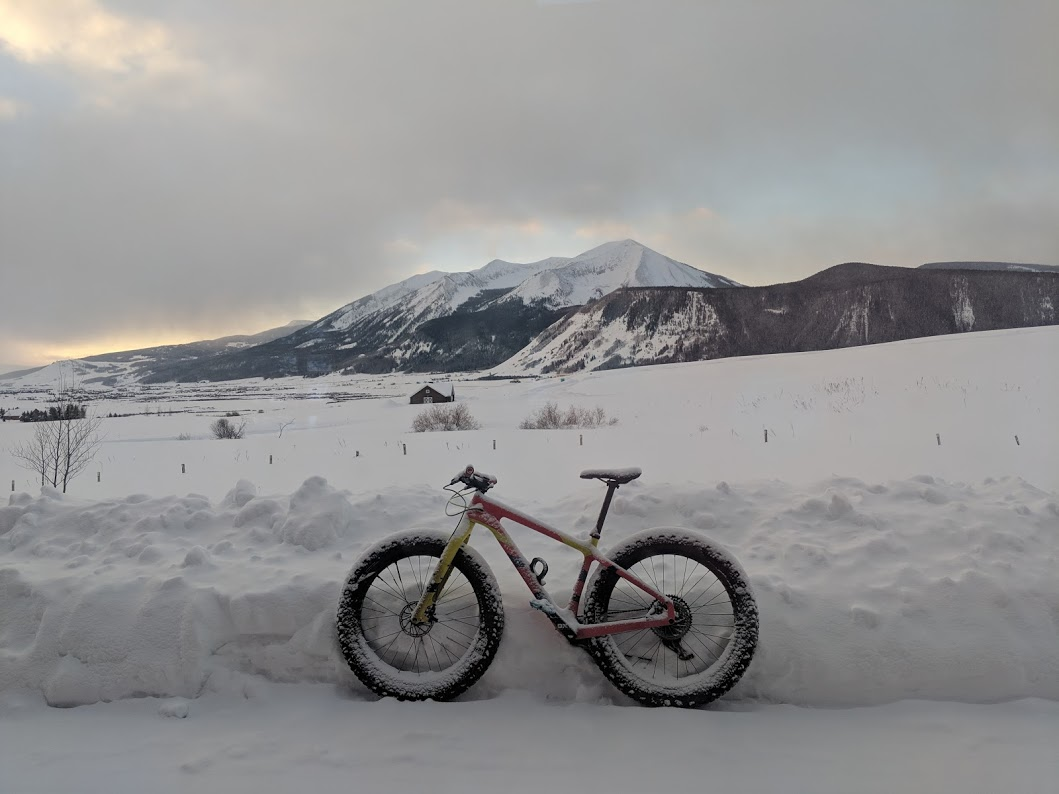 Salsa fat bike parked against a snow bank with snowy mountains in the background