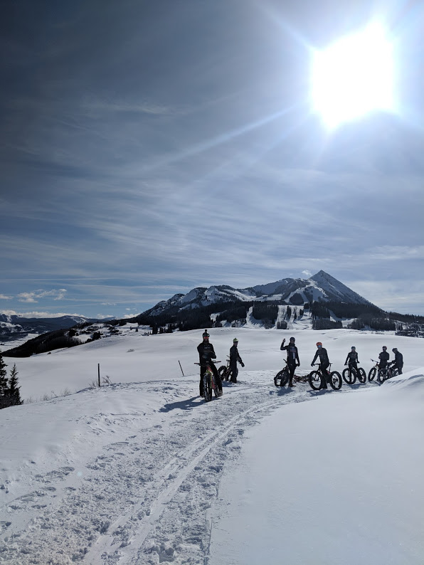 A group of fat bike cyclists on a snowy trail in front of mountain peaks