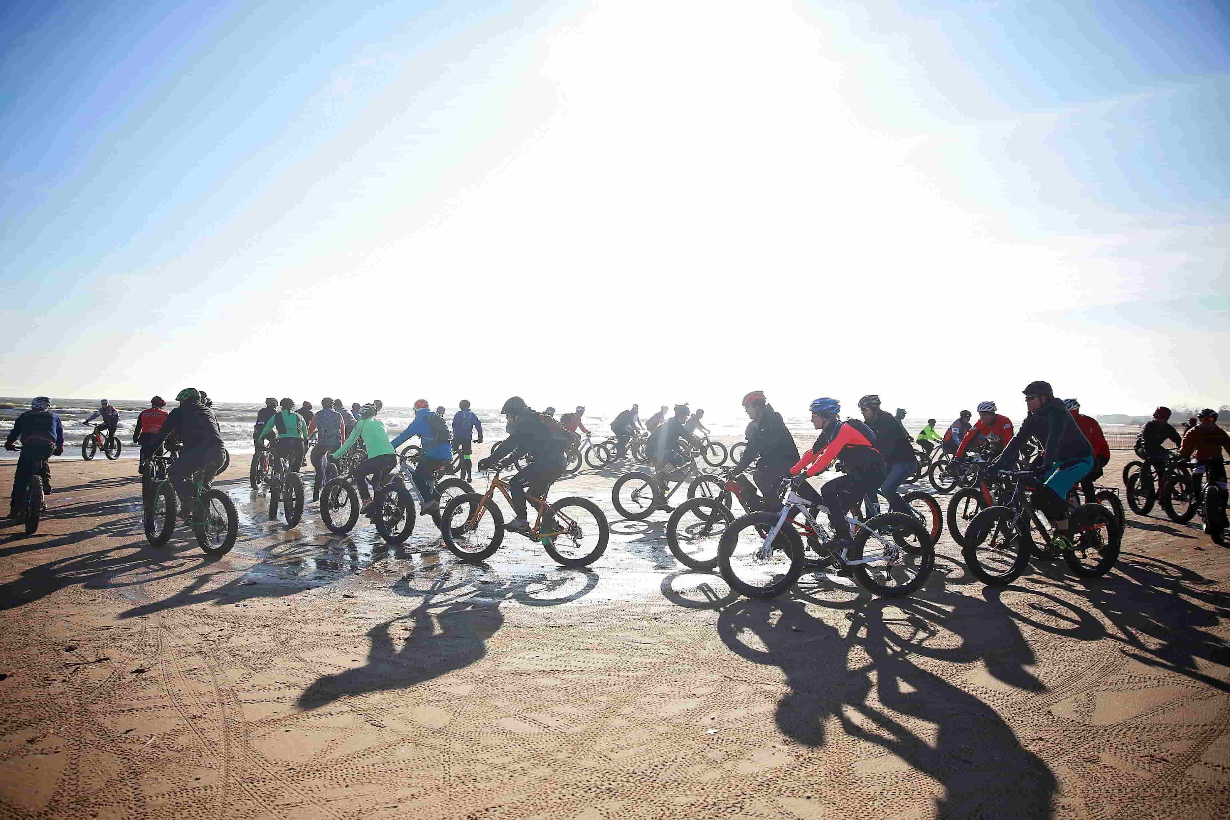 Dozens of fat bike cyclists riding on a beach on a sunny day in cold weather gear