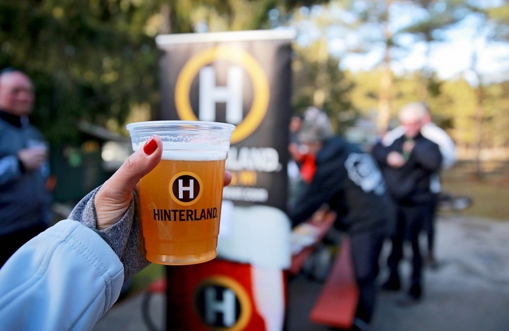 Hand holding a Hinterland plastic cup filled with beer at an outdoor event