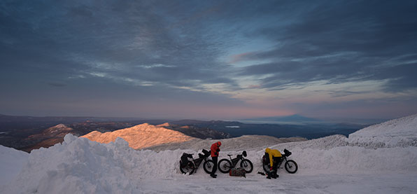 Two fat bike riders adjusting their winter cycling gear against snowy mountainous backdrop