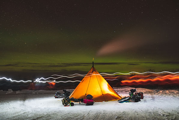 Campsite set up in the snow below the Northern Lights