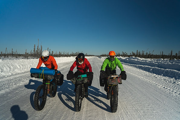 Three fat bike riders cycling on a deserted snow-covered road