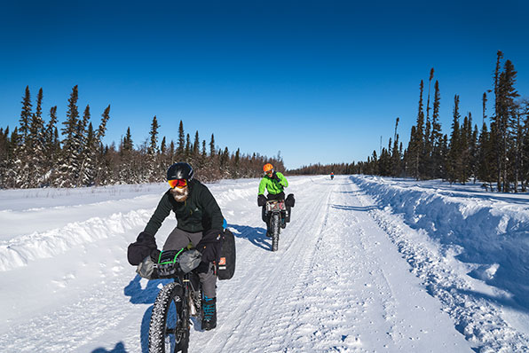 Two fat bike riders cycling on a deserted snow-covered road lined by trees