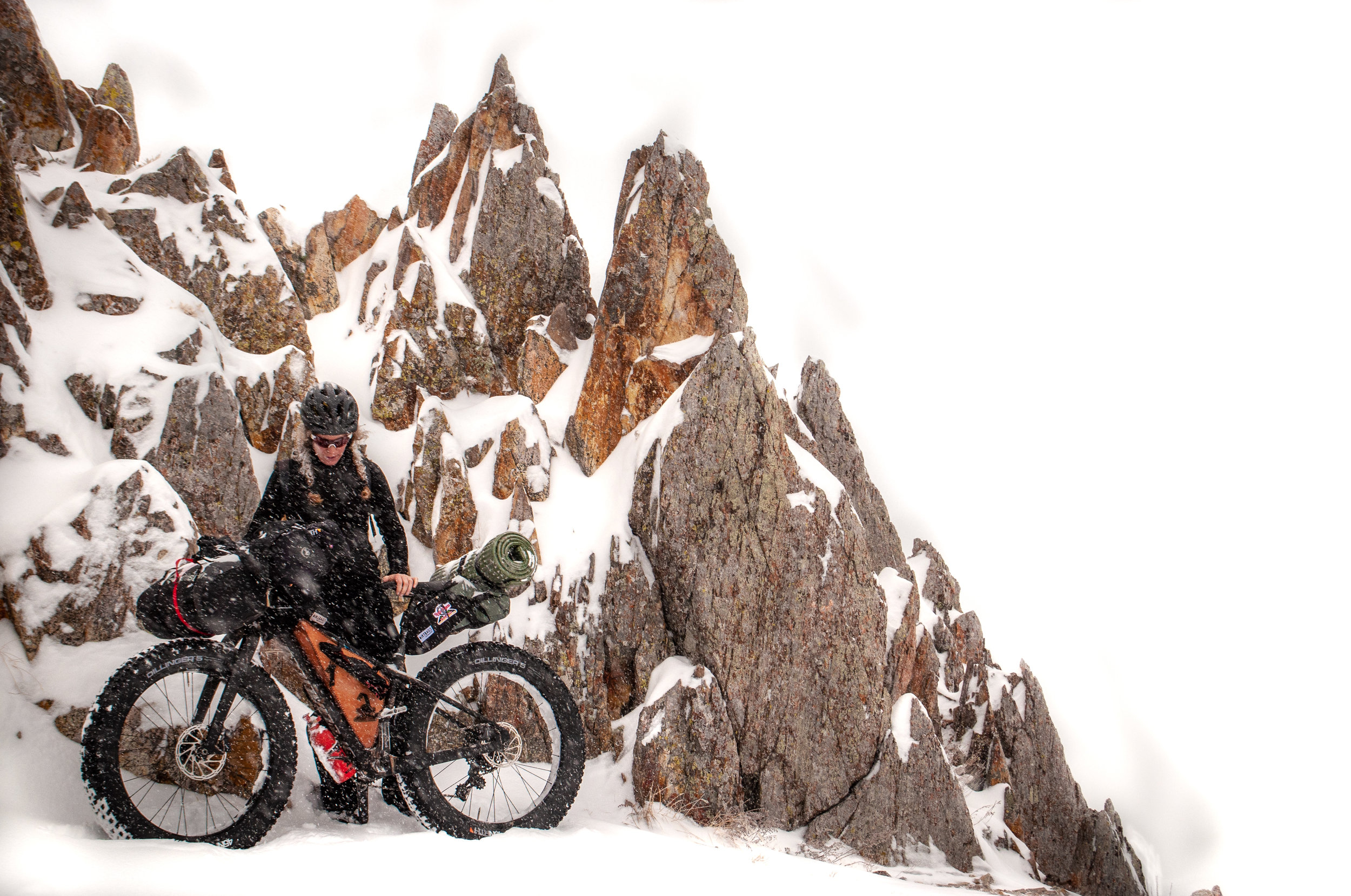 Fat bike rider with a loaded fat bike standing in front of snow covered rocks