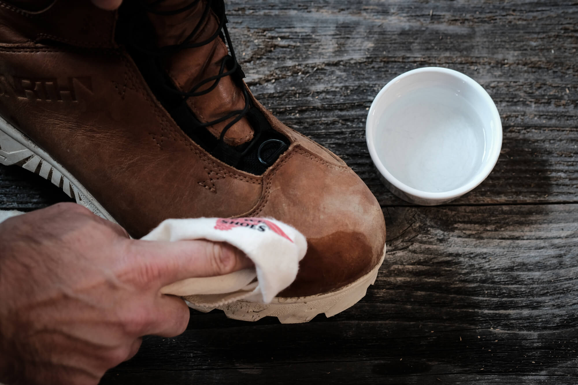 Wiping the 45NRTH Red Wing Wölvhammer cycling boot with a Red Wing cloth and small dish of water