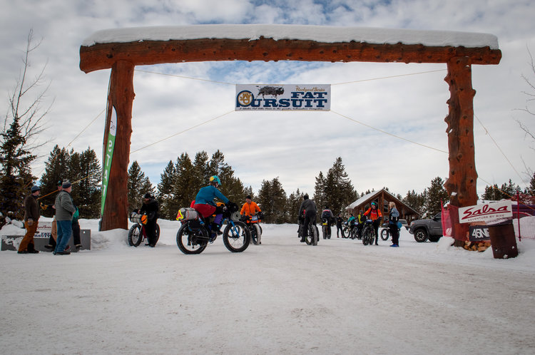 Several fat bike cyclists and civilians meandering below the Fat Pursuit start gate