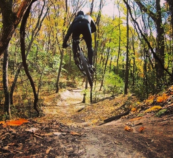 Person jumping a mountain bike on a dirt trail