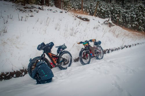 Two fat bikes parked alongside a trail with a rider checking tire pressure