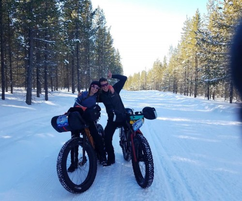 Michelle and Joel smiling and posing on their fat bikes on a snowy trail
