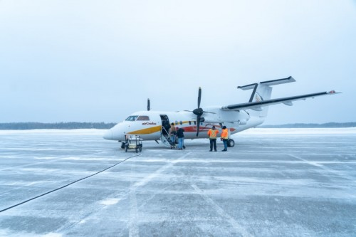 Riders boarding a small plane parked on snowy runway