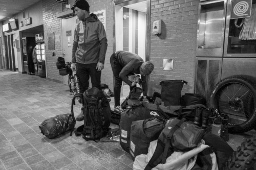 Two riders standing amongst gear and luggage in an airport