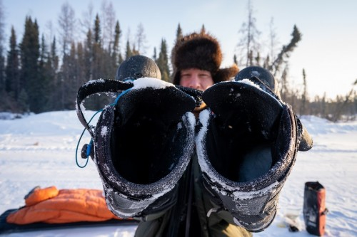 Rider holds his boots dusted with snow up to the camera