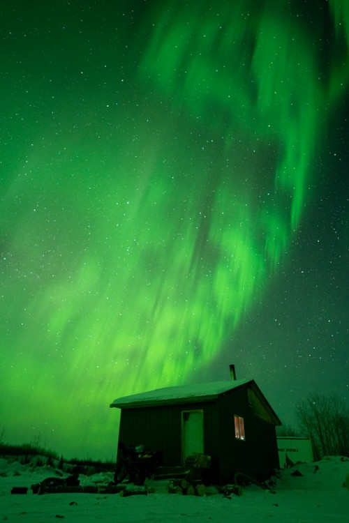 Small cabin with the Northern Lights on display in the sky