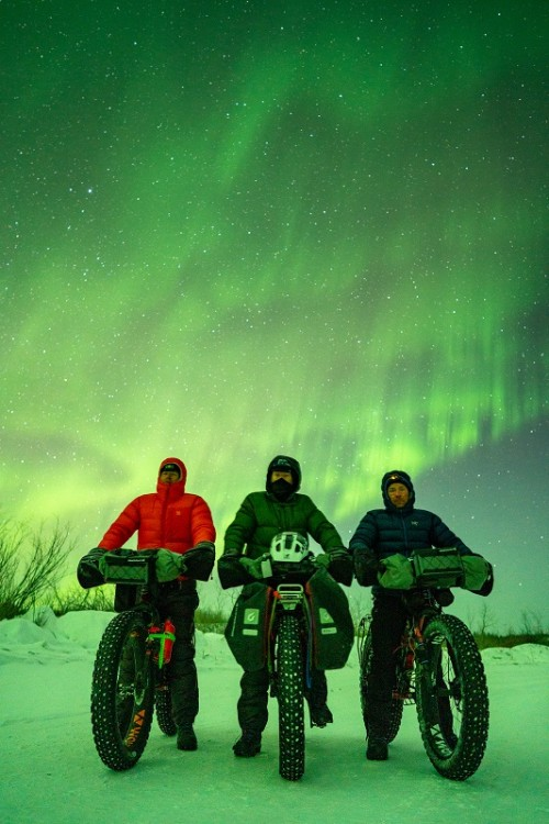 Three riders posed on their fat bikes with the Northern Lights on display in the sky