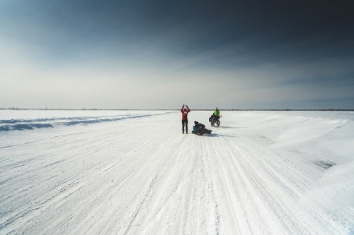 Two riders standing on a desolate snow covered road