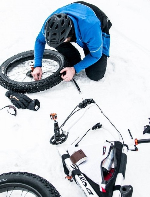 Fat bike rider changing a flat tire in the snow