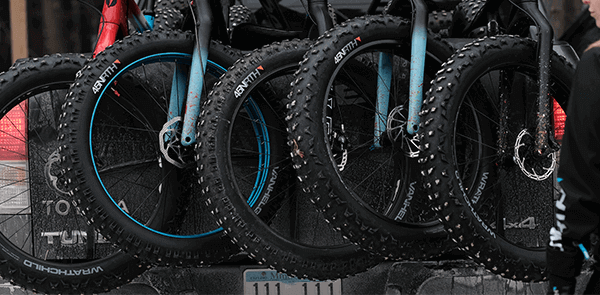 Several fat tire bikes lined up in a row with focus on the front 45NRTH fat bike tires.