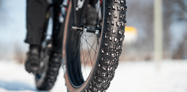 Closeup of a fat tire bike's front tire rolling over a frozen snow covered surface.
