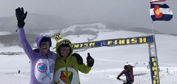 Two fat bike riders dressed in Care Bear costumes smiling in front of the finish line