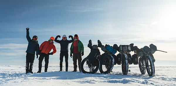 Four fat bike riders posing next to their loaded fat bikes in the snow