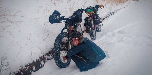 Fat bike rider smiling at the camera while checking the bike's front tire pressure