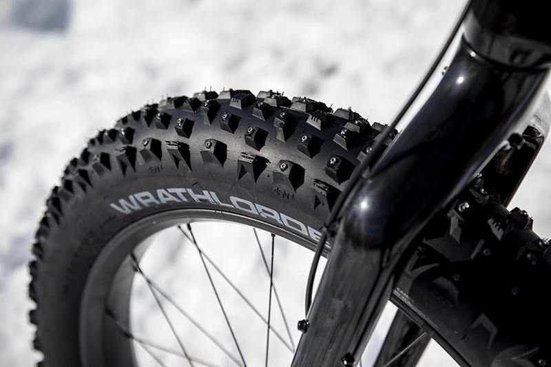 Closeup of a 45NRTH fat bike tire and front fork with snow covering the ground.