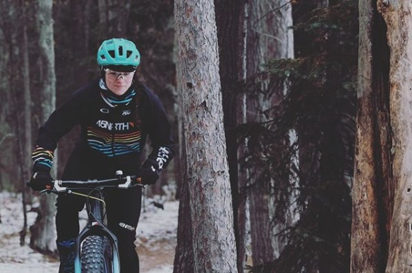 Person in a black 45NRTH jacket and blue helmet riding through snow and trees on a fat bike