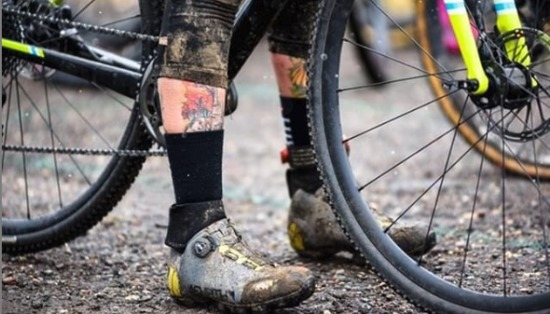 Two dirty legs with 45NRTH winter cycling boots planted on the ground straddling a bicycle