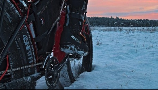 A person wearing 45NRTH boots on a fat bike stopped in a snowy field overlooking pine trees at dusk