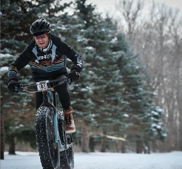 Person in a black 45NRTH jacket and black helmet riding through a snow covered trail on a fat bike