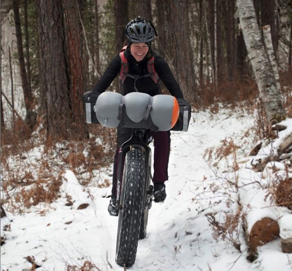 Person riding a fat bike through a snow cover trail with their hands in a pogie