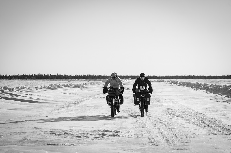 Two fat bike riders on a snow-covered trail