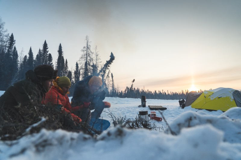 Three riders making coffee at snowy campsite in the morning