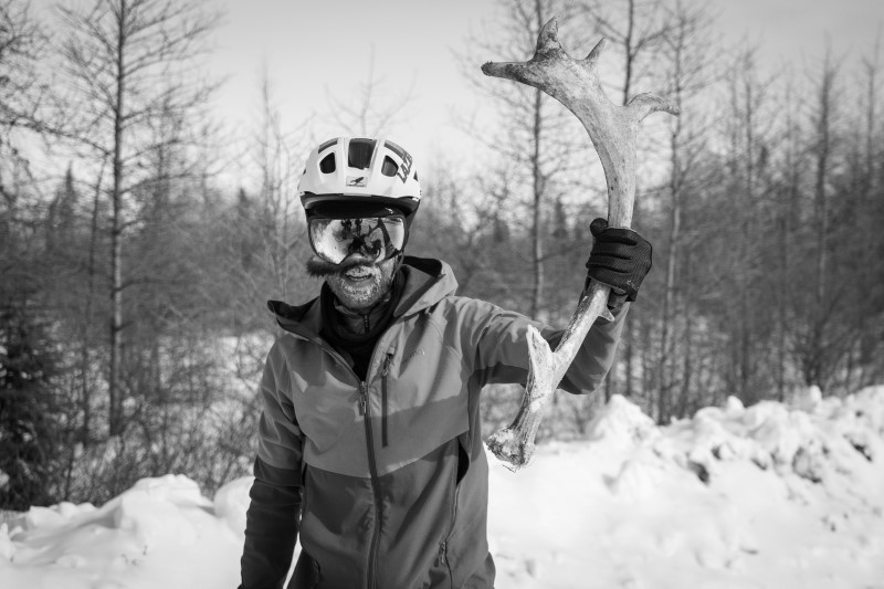 Rider standing against snowy tree-lined trail holding large caribou antler