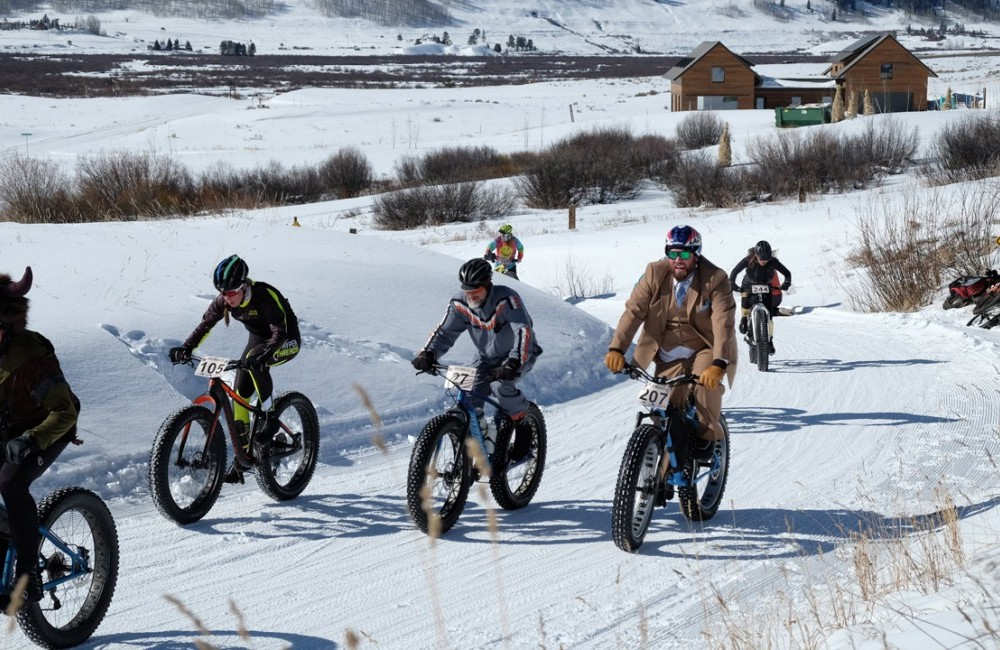Several fat bike riders on a groomed race course