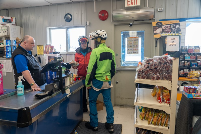 Riders in winter cycling gear making a purchase at a small general store