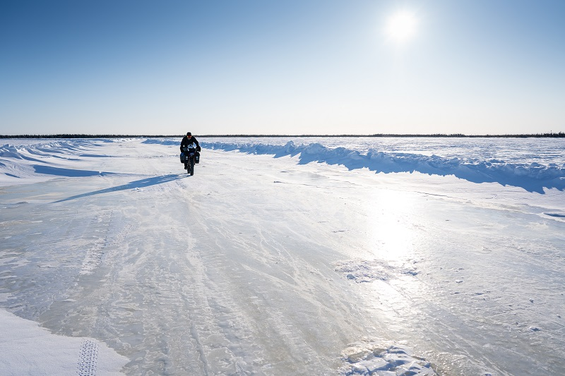 Ice-covered road with single fat bike rider